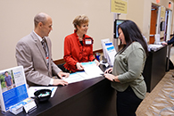 Thumbnail of: Three People Standing at Exhibit Booth