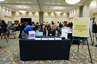 Thumbnail of: Two Women Sitting and Smiling at Wellness Works Exhibit Booth