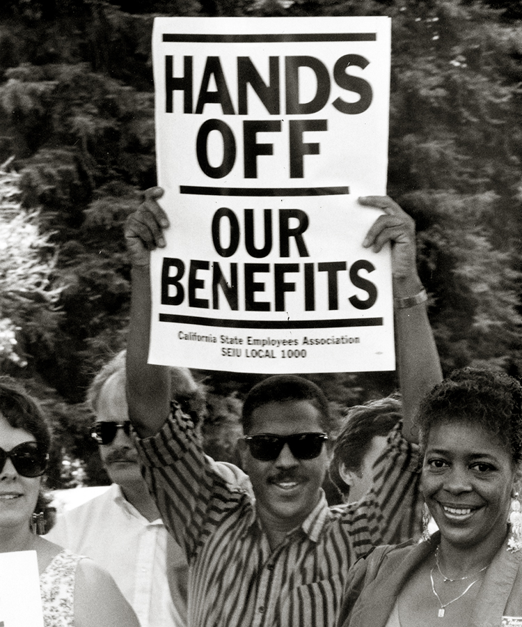Group of protesters. One protester is holding up a sign that says Hands Off Our Benefits.